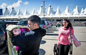 Photo - Mohammad Halabi wraps his daughter, Mia, 2, in a blanket Oct. 12 outside the Denver International Airport after his wife, daughter, son and mother arrived from New York. The family uprooted their lives in New York in order to give their daughter a chance at a normal life using a cannabis oil made from Charlotte's Web: a strain of marijuana high in cannabidiol that is thought to stop or reduce seizures. Photo by Michael Ciaglo, The Gazette