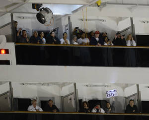 photo - People watch from their balconies and hold up signs aboard the Carnival Triumph after it was towed to the cruise terminal in Mobile, Ala., Thursday, Feb. 14, 2013. The ship with more than 4,200 passengers and crew members has been idled for nearly a week in the Gulf of Mexico following an engine room fire. (AP Photo/John David Mercer)