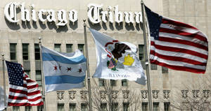 Photo - FILE - In this April 12, 2006 file photo, flags wave near the Chicago Tribune Tower in downtown Chicago. Chicago-based Tribune Co. says it wants to split its broadcasting and publishing businesses into two companies. The company owns 23 TV stations and cable network WGN America, along with the Chicago Tribune, Los Angeles Times and other newspapers. The newspapers would be spun off into an independent company to be called Tribune Publishing Co. (AP Photo/Charles Rex Arbogast, File)