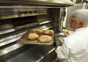 Photo - Prairie Thunder Baking Co. owner John McBryde removes loaves of great from a large oven recently at the Prairie Thunder Baking Co. in Oklahoma City. Photo By Paul Hellstern, The Oklahoman <strong>PAUL HELLSTERN - Oklahoman</strong>