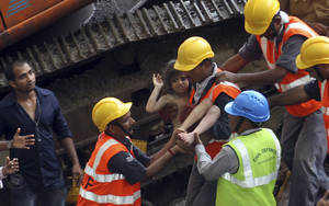Photo - Rescue workers carry a girl out from the rubble of a building that collapsed in Mumbai, India, Friday, Sept. 27, 2013. The apartment building collapsed in India's financial capital of Mumbai early Friday, killing people and sending rescuers racing to reach dozens of people trapped in the rubble. (AP Photo/Rajanish Kakade)