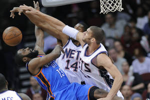 Photo - New Jersey Nets center Brook Lopez, right, and forward Derrick Favors blocks a shot by Oklahoma City Thunder guard James Harden, left, during the first quarter of an NBA basketball game Wednesday, Dec. 1, 2010, in Newark, N.J. (AP Photo/Bill Kostroun)