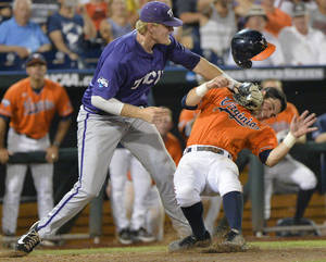 Photo - TCU first baseman Kevin Cron, left, tags out Virginia's Kenny Towns who was caught in a run down between third base and home plate in the eighth inning of an NCAA baseball College World Series game in Omaha, Neb., Tuesday, June 17, 2014. (AP Photo/Ted Kirk)