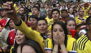 Photo - Colombia soccer fans cheer during their team's soccer World Cup game against Greece in Bogota, Colombia, Saturday, June 14, 2014. Colombia defeated Greece 3-0. (AP Photo/Javier Galeano)