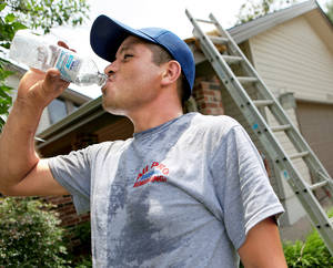 Photo - Hector Ochoa, an employee at All Pro Roofing and Remodeling, takes a water break Wednesday after working on a roof in Oklahoma City. Temperatures were in the lower 90s Wednesday in the metro area and are  expected to be so again today. Photo by John Clanton, The Oklahoman