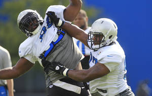 Photo - Detroit Lions defensive end Ronnell Lewis, right, stiff arms Detroit Lions defensive tackle Andre Fluellen during NFL football training camp in Allen Park, Mich., Tuesday, July 31, 2012. (AP Photo/Carlos Osorio) ORG XMIT: MICO108