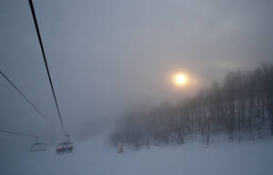 Photo - The sun tries to break through the heavy fog as skiers take a chair lift up the mountain near the alpine skiing training slopes at the Sochi 2014 Winter Olympics, Monday, Feb. 17, 2014, in Krasnaya Polyana, Russia. (AP Photo/Christophe Ena)