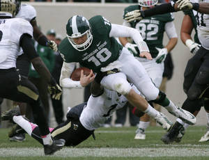Photo - Michigan State quarterback Connor Cook, top, is stopped on a keeper by Purdue's Normondo Harris during the fourth quarter of an NCAA college football game, Saturday, Oct. 19, 2013, in East Lansing, Mich. Michigan State won 14-0. (AP Photo/Al Goldis)