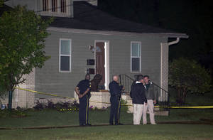 Photo - Members of the Tuscaloosa Police Department stand outside of the home where Alabama student John Servati died after taking refuge from a storm on Monday,  April 28, 2014. Servati, who was from Tupelo, Miss., was a member of the Alabama swim team. (AP Photo/The Tuscaloosa News, Robert Sutton)