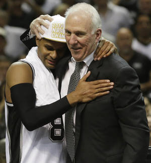 Photo - San Antonio Spurs guard Patty Mills (8) and head coach Gregg Popovich embrace after Game 5 of the NBA basketball finals on Sunday, June 15, 2014, in San Antonio. The Spurs won the NBA championship 104-87. (AP Photo/David J. Phillip)