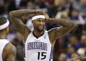 Photo - Sacramento Kings center DeMarcus Cousins reacts after getting hit in the side of the head during the first quarter of an NBA basketball game against the Chicago Bulls in Sacramento, Calif., Monday, Feb. 3, 2014. (AP Photo/Rich Pedroncelli)