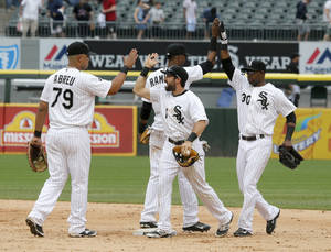 Photo - Chicago White Sox players, from left, Jose Abreu, Alexei Ramirez, Adam Eaton, and Alejandro De Aza celebrate their 7-6 win over the San Francisco Giants in an interleague baseball game Wednesday, June 18, 2014, in Chicago. (AP Photo/Charles Rex Arbogast)