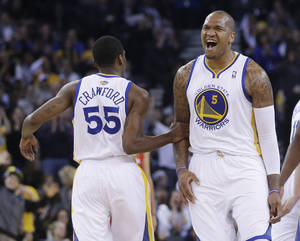 Photo - Golden State Warriors' Marreese Speights (5) celebrates after teammate Jordan Crawford (55) made a 3-point basket against the Los Angeles Clippers during the first half of an NBA basketball game Thursday, Jan. 30, 2014, in Oakland, Calif. (AP Photo)