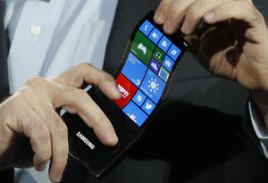 photo - Eric Rudder, chief technical strategy officer of Microsoft, holds a prototype Windows smartphone with a flexible OLED display during Samsung's keynote address at the International Consumer Electronics Show in Las Vegas, Wednesday, Jan. 9, 2013. (AP Photo/Jae C. Hong)