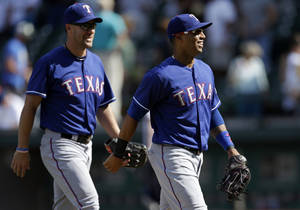Photo - Texas Rangers' Leonys Martin, right, and David Murphy, left, walk together off the field after the Rangers beat the Seattle Mariners 12-4 in a baseball game, Wednesday, Aug. 28, 2013, in Seattle. (AP Photo/Ted S. Warren)