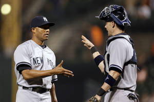 Photo - New York Yankees relief pitcher Mariano Rivera, left, shakes hands with catcher Chris Stewart after a baseball game against the Baltimore Orioles, Thursday, Sept. 12, 2013, in Baltimore. New York won 6-5. (AP Photo/Patrick Semansky)