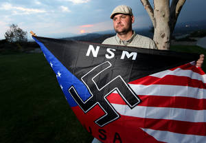 Photo - FILE - In this Oct. 22, 2010 file photo, Jeff Hall, who was killed by his son, holds a Neo Nazi flag while standing at Sycamore Highlands Park near his home in Riverside, Calif. Defense attorneys for a boy charged with killing Hall, his neo-Nazi father when he was 10 years old has rested its case without calling the boy to testify, Wednesday, Jan. 9, 2013. (AP Photo/Sandy Huffaker, File)
