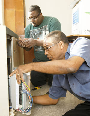 Photo - HVAC technicians Thomas Lacey, left, and his father, Stephen Lacey, work on an air conditioning unit Tuesday at the Classen School of Advanced Studies in Oklahoma City. Photo By Paul Hellstern, The Oklahoman
