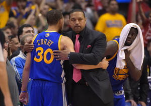 Photo - Golden State Warriors head coach Mark Jackson, center, hugs guard Stephen Curry after Curry was taken out of the game as forward Draymond Green looks on during the second half in Game 7 of an opening-round NBA basketball playoff series, Saturday, May 3, 2014, in Los Angeles. The Clippers won 126-121. (AP Photo/Mark J. Terrill)