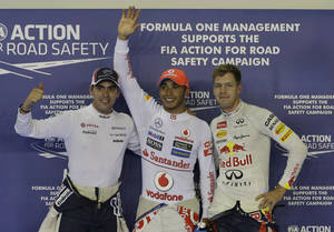 Photo -   McLaren Formula One driver Lewis Hamilton, centre, of Britain waves after winning the qualifying session for the Singapore Formula One Grand Prix on the Marina Bay City Circuit in Singapore, Saturday, Sept. 22, 2012. Williams Formula One driver Pastor Maldonado, left, of Venezuela was second fastest and Red Bull Formula One driver Sebastian Vettel of Germany third for tomorrows race. (AP Photo/Dita Alangkara)