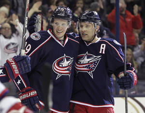 Photo - Columbus Blue Jackets' Ryan Johansen, left, and Jack Johnson celebrate Johansen's goal against the Washington Capitals during the second period of an NHL hockey game, Thursday, Jan. 30, 2014, in Columbus, Ohio. (AP Photo/Jay LaPrete)
