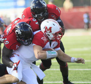 Photo - Miami (Ohio) quarterback Austin Boucher (16) is tackled by Cincinnati's Jeff Luc, left, and Arryn Chenault during the first half of an NCAA college football game, Saturday, Sept. 21, 2013, in Oxford, Ohio. (AP Photo/Tony Tribble)