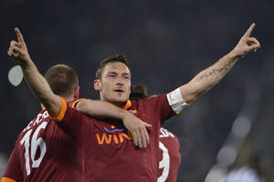 photo - AS Roma's Francesco Totti, center, hugged by teammate Daniele De Rossi, celebrates after scoring during a Serie A soccer match between AS Roma and Juventus at Rome's Olympic stadium, Saturday, Feb. 16, 2013. (AP Photo/Alfredo Falcone, LaPresse)