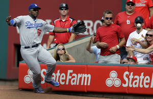 Photo - Los Angeles Dodgers right fielder Yasiel Puig cannot reach a foul ball hit by St. Louis Cardinals' Jhonny Peralta during the third inning of a baseball game Saturday, July 19, 2014, in St. Louis. (AP Photo/Jeff Roberson)