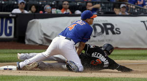 Photo - New York Mets third baseman Wilmer Flores, left, tags out Miami Marlins' Adeiny Hechavarria at third base during the ninth inning of the baseball game at Citi Field, Sunday, Sept. 15, 2013, in New York. (AP Photo/Seth Wenig)