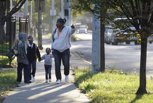 photo -   Leslie Sabbs-Kizer, right, walks her children Nkai Melton, 8, Akaira Melton, 7, and Khaymya Smith, 3 to Bond Elementary school in Chicago, Wednesday morning, Sept. 19, 2012, after Chicago teachers voted to suspend their first strike in 25 years. Union delegates voted overwhelmingly Tuesday night to suspend the walkout after discussing a proposed contract settlement with the nation's third largest school district. (AP Photo/M. Spencer Green)