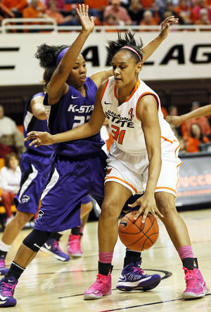 Photo - OSU's Kendra Suttles, right, works against Kansas State's Mariah White at Gallagher-Iba Arena on Saturday. Suttles scored 19 points and had 10 rebounds.