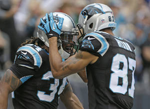 Photo - Carolina Panthers' DeAngelo Williams (34) is congratulated by teammate Domenik Hixon (87) after his touchdown run against the New Orleans Saints in the first half of an NFL football game in Charlotte, N.C., Sunday, Dec. 22, 2013. (AP Photo/Bob Leverone)