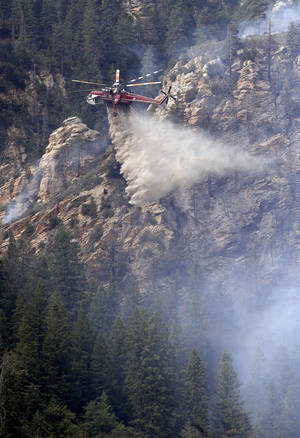 Photo - A Heavy Type-1 Skycrane Helictoper dumps 2,000 gallons of water on the Slide Fire as it burns up Oak Creek Canyon on Friday, May 23, 2014, near Flagstaff, Ariz.  The fire has burned approximately 7,500 acres. (AP Photo/Ross D. Franklin)