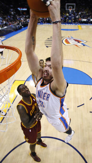 Photo - Oklahoma City Thunder center Byron Mullens, right, who was recalled from the NBA Development League prior to the game, dunks in front of Cleveland Cavaliers forward J.J. Hickson, left, in the fourth quarter of an NBA basketball game in Oklahoma City, Sunday, Dec. 12, 2010. Oklahoma City won 106-77.(AP Photo/Sue Ogrocki)