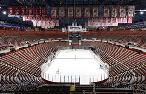 photo - In this photo taken Tuesday, Dec. 18, 2012, championship banners and retired numbers of the Detroit Red Wings hockey team hang from the rafters above the ice at Joe Louis Arena in Detroit. The NHL lockout that's already wiped out the first three months of the season is taking its toll on small businesses in many of the NHL's markets. (AP Photo/Paul Sancya, File)