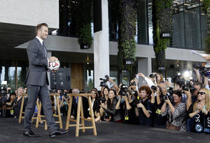 Photo - Former England soccer star David Beckham holds a soccer ball at a news conference where he announced he will exercise his option to purchase a Major League Soccer expansion team in Miami, Wednesday, Feb. 5,  2014, in Miami. (AP Photo/Lynne Sladky)