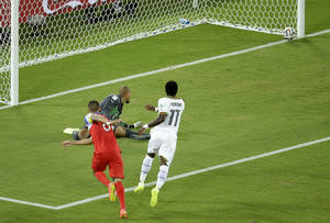 Photo - United States' Clint Dempsey, left, scores the opening goal past Ghana's goalkeeper Adam Kwarasey, center, during the group G World Cup soccer match between Ghana and the United States at the Arena das Dunas in Natal, Brazil, Monday, June 16, 2014. (AP Photo/Hassan Ammar)