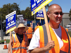 Photo - Truck drivers and supporters picket outside the offices of Green Fleet Systems in Carson, Calif., on Monday, July 7, 2014. The truckers say the companies have prevented them from unionizing and improperly classified them as contractors, rather than full-time employees, to minimize wages and benefits. (AP Photo/Matt Hamilton)
