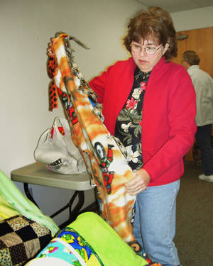 Photo - Chris Reed sorts blankets at a Project Linus meeting in Tuttle Tuesday. Reed is the project coordinator of the Norman chapter.  Photo by Tami Althoff/The Oklahoman