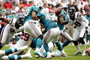 photo -   Miami Dolphins running back Daniel Thomas (33) fumbles the ball as he is hit by Houston Texans strong safety Glover Quin (29) in the second quarter of an NFL football game, Sunday, Sept. 9, 2012, in Houston. The Texans recovered the fumble. (AP Photo/Dave Einsel)