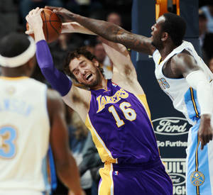Photo - Los Angeles Lakers center Pau Gasol (16), of Spain, pulls in a rebound as Denver Nuggets forward Jordan Hamilton covers in the first quarter of an NBA basketball game in Denver on Wednesday, Nov. 13, 2013. (AP Photo/David Zalubowski)