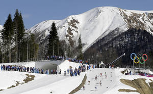 Photo - Competitors ski past the Olympic rings during the women's 4x5K cross-country relay at the 2014 Winter Olympics, Saturday, Feb. 15, 2014, in Krasnaya Polyana, Russia. (AP Photo/Kirsty Wigglesworth)