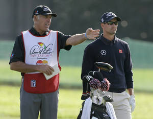 Photo - Caddie Steve Williams, left, gestures as he talks to Adam Scott, of Australia, on the 16th fairway during the first round of the Arnold Palmer Invitational golf tournament at Bay Hill Thursday, March 20, 2014, in Orlando, Fla. (AP Photo/Chris O'Meara)