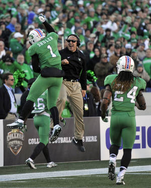 Photo - Marshall's Tommy Schuler, left, celebrates after scoring a touchdown with coach Mike Furrey in the first half of the Military Bowl NCAA college football game against Maryland, Friday, Dec. 27, 2013, in Annapolis, Md.(AP Photo/Gail Burton)