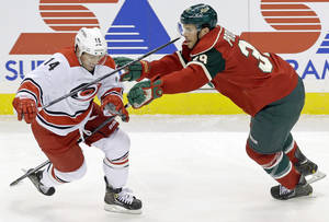 Photo - Minnesota Wild's Nate Prosser, right, tries to slow up Carolina Hurricanes' Nathan Gerbe in the first period of an NHL hockey game, Thursday, Oct. 24, 2013, in St. Paul, Minn. (AP Photo/Jim Mone)