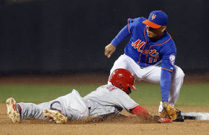 Photo - New York Mets shortstop Ruben Tejada (11) tags out Cincinnati Reds Billy Hamilton who was trying to steal second base in the eighth inning of a baseball game at Citi Field in New York, Friday, April 4, 2014. The Mets won 4-3. (AP Photo/Paul J. Bereswill)