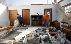 Photo - Pam and Terry Nelson sort through items inside the Woodward home of his mother, Wilma Nelson, after a tornado hit the house Sunday. Wilma Nelson also survived a tornado in Woodward in 1947. Photo by Bryan Terry <strong>BRYAN TERRY - THE OKLAHOMAN</strong>