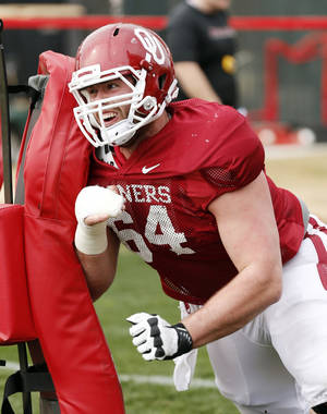 Photo - OU center Gabe Ikard said after practice Monday that he's participating in individual drills, but can't do much else because of his broken hand.  PHOTO BY STEVE SISNEY, The Oklahoman