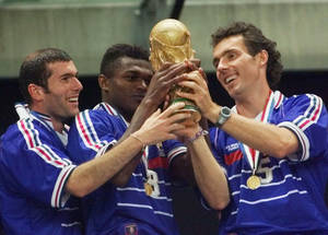 Photo - FILE - In this Sunday, July 12, 1998 file photo, French teammates from left, Zinedine Zidane, Marcel Desailly and Laurent Blanc hold the soccer World Cup after France defeated Brazil 3-0 in the World Cup final soccer match, at the Stade de France in Saint Denis. On this day, France wins its first World Cup after defeating Brazil 3-0, following 2 headed goals from Zidane and a late strike from Emmanuel Petit. (AP Photo/Michel Euler, File)