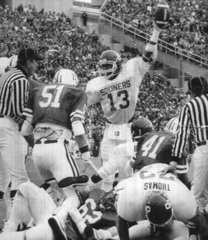 Photo - OU's Steve Sewell celebrates the touchdown by Danny Bradley (no 1 on back of helmet on ground) against Nebraska. Staff photo by Jim Argo.